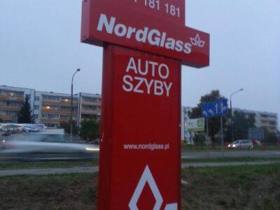 Pylon z tablicą reklamową przy stacji w Białymstoku
